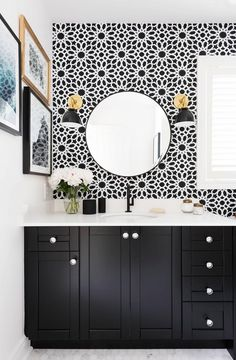Black and white bathroom with vase of flowers, small gallery wall, round mirror, black and gold wall sconces, and floral wallpaper