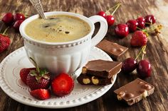 cup of freshly brewed coffee, chocolate and fruit on the old wooden background. rustic style. selective focus