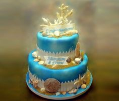 Cake is decorated with chocolate seashells, royal icing coral, fondant fence, sanding sugar, and airbrushed.