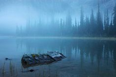 Picture of a misty Mary Lake with a backdrop of evergreens covered in fog and a rock peeking out of the water