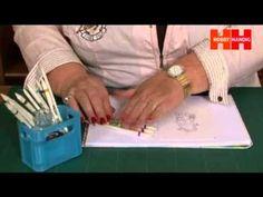 Diny Sprakel adviseert over het inkleuren van stempelfiguren met Derwent potloden en burnishers. Ze maakt daarbij gebruik van kleurkaarten, doezelaars en Spica glitterpennen.