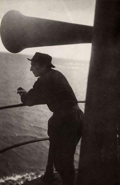 Klederdrachten : Tijdens een bezoek van Koningin Wilhelmina aan Urk staat een man in traditionele kleding bij een grote misthoorn. 1921 #Urk