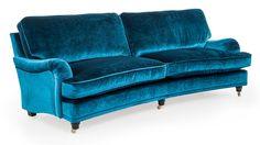 En lyxig mörkblå howardsoffa i sammetstyg med vackra färgskiftningar i klarblått. Tekniken att väva sammet är över 800 år gammal och tyget har sedan dess varit en återkommande trend inom heminredning.Sittkuddarna är stoppade med dun runt en kallskumskärna,vilket är det absolut bästa eftersom formen bevaras samtidigt som soffan blir otroligt skön att sitta i.