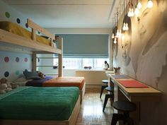 Suspended light bulbs and an oversized photo mural keep desks free of lamps and photographs, while bunk beds provide extra space for kids to work and play.—Cortney Novogratz, designer, The Novogratz and star of HGTV's Home by Novogratz