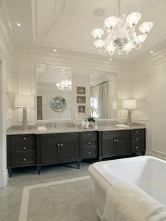 Tradition bathroom features tray ceiling accented with glass chandelier hanging over freestanding ...
