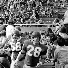 Black and white photo of University of Oregon football players Ken Woody (#28) and Rick Willmore (#58) running onto the field with the rest of the team for a game against Idaho on October 17, 1970. The Ducks won the game 49-13. ©University of Oregon Libraries - Special Collections and University Archives