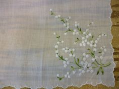 This beautiful vintage hanky is made of thin white cotton with a large bouquet of lily of the valley in one corner, and small sprigs of lily