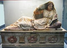 Etruscan Sarcophagos, painted marble.  Seianti Hanuvia Tlesnasa, peering into her mirror, reclines on the lid; her clothing and jewelry mark her as a noblewoman. The front of the sarcophagos is decorated with rosettes and triglyphs. From Poggio Cantarello near Chiusi. Etruscan c. 150-30 BCE. London, British Museum.