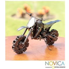 By Armando Ramirez, this handsome motocross bike sculpture is handcrafted of recycled metal and auto parts. A car's rocker arm, clutch, chains and a sparkplug find a new life in the rustic sculpture.