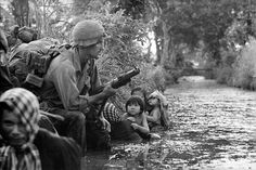 Two South Vietnamese children gaze at an American paratrooper holding an M79 grenade launcher as they cling to their mothers who huddle against a canal bank for protection from sniper fire in the Bao Trai area, Vietnam, 1966.