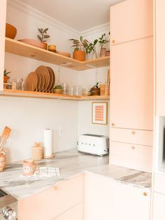 Modern kitchen with pink cabinets, marble countertop, brass round knobs, white sink and faucet and wooden shelves. A boho look is added with the shelf decor. Modern Farmhouse Kitchens, Farmhouse Kitchen Decor, Kitchen Interior, Home Kitchens, Kitchen Design, Kitchen Modern, Interior Modern, Smeg Kitchen, Boho Kitchen