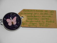 Pillsbury?s Pieces No, 163.  Pin - metallic purple capsule with pale lilac paper butterfly.  In exchange for a donation to KATHMANDU ANIMAL TREATMENT CENTRE, Nepal.  Available at St. George's Church, Madrid on Saturday 13 June from 11.00 - 15.00.