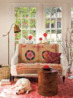 Earthy, contemporary, old world.  Vintage suzani tapestry, Madeline Weinrib rug, and organic accents.
