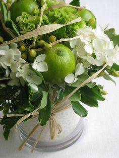 Shiny limes, hydrangeas in white, pale berries, three types of foilage with raffia tie on vase and woven through.