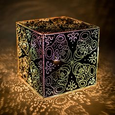 Perfect for the nightstand or corner table, these sophisticated motifs stand out on this handmade classic lamp. Delicate patterns handcrafted the old fashioned way, in a workshop in Tunisia.  Color: Black Aluminum  Dimensions: L: 12'' x W: 12''