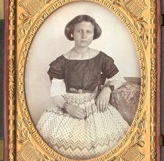 Quarter plate daguerreotype of an attractive young lady in front of white background, anonymous American ca. 1855. Housed as found in a black geometric thermoplastic case. With tinting in red and blue to the tablecloth and red to her lips