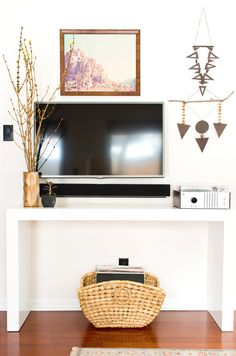 Console table styled with branches, a TV, and small wall decals