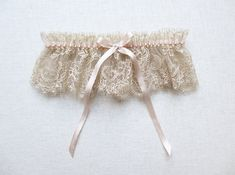 *Limited edition*    Beautiful garter made from nude taupe French lace and blush silk. This glamorous garter is adorned with a blush silk bow &
