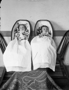 Studio portrait of deceased twin infants in coffins. They are Robert  and Janet Fitzpatrick, born July 5, 1885, and died April 20, 1886,  children of Robert and Martha Fitzpatrick.