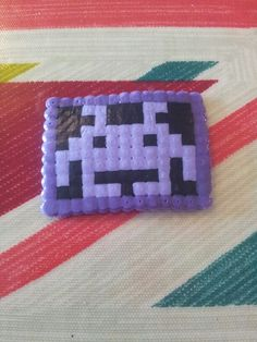 Space invader made out of purple, dark purple and black hama beads.
