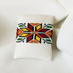 Loom beaded cuff bracelet with Ukrainian ethnic ornament on white background in green, yellow, orange and brown shades. This pattern carries an Ukrainian folk c Loom Bracelet Patterns, Bead Loom Patterns, Beading Patterns, Beading Ideas, Beaded Cuff Bracelet, Bead Loom Bracelets, Beaded Jewelry, Loom Beading, Bead Weaving