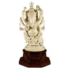 A large Indian carved ivory figure of Ganesh with attributes, on rosewood stand. Height: 40cm