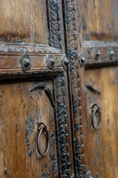 Pair of tall Spanish Colonial entrance doors fit together to show an arch. Still has it's original metal hardware. The aged look that it carries offer a tremendous amount of history. Shows ware that's consistent with age and use.