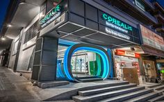 The impressive façade and the colorful interior of the new COREALIS store becomes a magnet for all the visitors of the busy square of Nea Smyrni. Contracting Company, Commercial Construction, The Visitors, Athens, Colorful Interiors, Facades, Store, Projects, Tent
