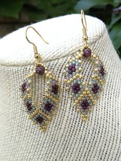 The earrings are already made and ready to ship. *** Please note that maroon is a hard color to photograph. I tried my best to represent the colors found in this earring. Matte maroon, opalescent light purple and metallic gold colored Japanese glass seed beads are hand stitched together using the peyote technique creating a leaf shape. The opalescent light purple bead reminds me of a soap bubble with a slight purple tint to it. SIZING: The beaded portion of the earring is approximately 1…