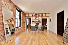 an enchanting exposed brick wall idea for stunning living room with lacquered flooring and large mirror with exclusive furnitures and built in wooden bookshelf