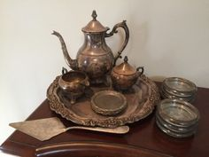 "VINTAGE GROUPING OF SILVERPLATE INCLUDING A TRAY, TEAPOT, CREAMER, SUGAR, CAKE SERVER, COASTERS, ETC. GLASS LINED COASTERS ARE MARKED ""LEONARD ITALY SILVERPLATE""."