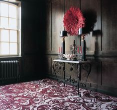 dark olive walls, a red feather headdress and scrolled iron console table
