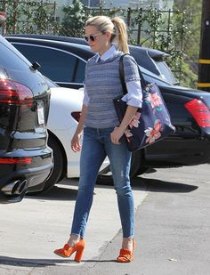 Reese Witherspoon wears a button down under a tweed shirt with a floral printed bag, skinny jeans, and Gucci Marmont Fringe Suede Loafers for a pop of color