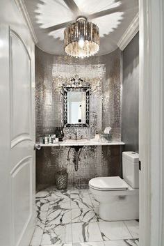 I love all the shiny mirror tiles and reflection on the ceiling from the chandelier in this powder room!