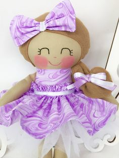 Rag Dolls are so lovable! This is a 14 inch Cloth Doll that is part of the Dressy Doll collection from Sew Many Pretties.  This is plush doll is handmade from 100% cotton fabrics and wool blend felt for her hair. Facial features are hand embroidered. Her hair bows are sewn securely.  This plush doll has fabric skirt with a Velcro closure in the back that makes it easy for a young child to dress her with. To dress your doll up even more you have the option of adding on a white tulle…