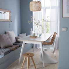 Une banquette intégrée dans la salle à manger. Lorsque l'espace ne permet pas d'installer une ribambelle de chaises autour de la table, il suffit de créer une banquette. Empilez-y des coussins aux couleurs neutres et naturelles et vous créerez en un clin d'œil un coin repas cosy aux accents bohème.