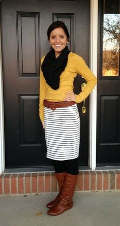 Yellow sweater, black cowl scarf, striped skirt, black tights with camel color boots  belt