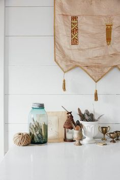 This tiny cottage-style cabin from Paige Morse makes great use of available space and features nature-themed eclectic decor such as a framed leaf and a hanging stick.