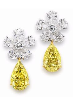 A pair of diamond cluster earrings, by Graff.   Each pear-shaped fancy deep yellow diamond, weighing 2.53 and 2.35 carats, suspended from a pear and brilliant-cut diamond surmount, clusters by Graff, fancy coloured diamonds later added.  Via Bonhams.