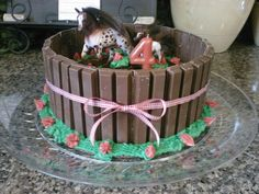 Horse themed birthday cake - I am by no means a cake decorator, so this idea could definately be excuted so much better!  I just used a single layer cake for the horse pasture, kit-kats for the fence, and then added a little grass & flowers, a candle, a horse figurine and a ribbon to top it all off.  My daughter loved it, despite my lack luster artistic cake decorating skills :-)