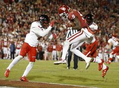 Oklahoma's CeeDee Lamb (9) catches a touchdown pass between Texas Tech's Jah'Shawn Johnson (7) and Douglas Coleman III (25) during a college football game between the Oklahoma Sooners (OU) and the University of Texas Tech Red Raiders (TTU) at Gaylord Family-Oklahoma Memorial Stadium in Norman, Okla., Saturday, Oct. 28, 2017. Photo by Bryan Terry, The Oklahoman