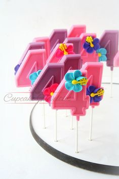 Buy Online! Perfect dessert and/or party favors for your Tropical party, Moana Birthday Party, Luau Party or a Tahitian themed party! Delicious Number shaped Chocolate pops in purple and pink chocolate topped with handmade colorful hibiscus flowers!