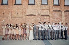 mismatched bridal party. all bridesmaids wearing dresses in the same color scheme and all groomsmen wearing gray slacks