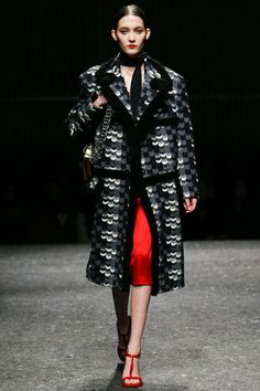 Black and grey print coat with fur trim paired with red skirt by Prada. #IStyleNY #Style