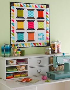 If you don't have room to spread out, think about spreading up. Stack storage compartments on your sewing table to keep supplies at hand. Open shelving hold fabric, while closed drawers stash rulers and scissors. Place clear jars filled with thread and buttons on top to create a bright and organized space.