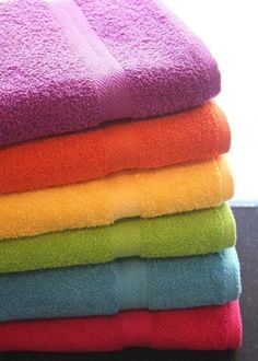 Bright colored towels in purple, orange, yellow, green, blue and pink.