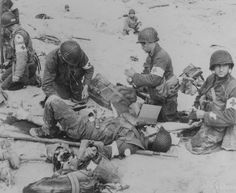 """""""American Medics render first aid to troops in the initial landing on Utah Beach. Les Dunes de Madeleine, Northern Coast, France. In the background other members of the landing parties dig into the soft sand of the beach. June 6, 1944"""" (US National Archives) 4th Infantry Division"""