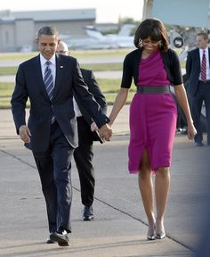 The President and First Lady flew to Dallas, Texas today, where they will join former presidents in inaugurating the presidential library and museum of George W. Bush. Arriving at Dallas Love Field Airport, Mrs. O wore a pink draped neck dress (a new frock, perhaps?) paired with a black belt and cropped cardigan. Silver heels completed the look.