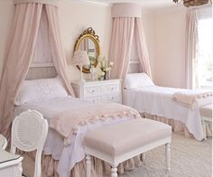 shared bedroom design in french style, supplemented by twin canopy bed, a white sideboard, a beautiful table lam, a gold framed mirror, a white desk and a white desk chair