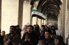 Activists in Aleppo carry a flag during a demonstration inside the Umayyad mosque to mark the three-year anniversary of the Syrian uprising.